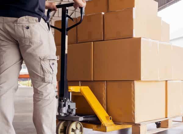 คนงานในโกดัง-ขนสินค้า-กล่อง-บนรถลากพาเลท